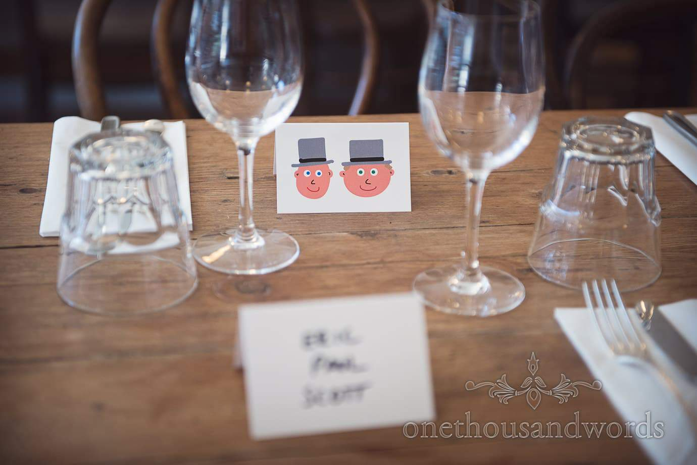 Pre-wedding meal table place name signs with cartoon grooms heads in top hats
