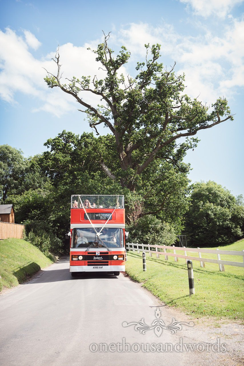 Red open top wedding bus drives through Dorset countryside on summers day