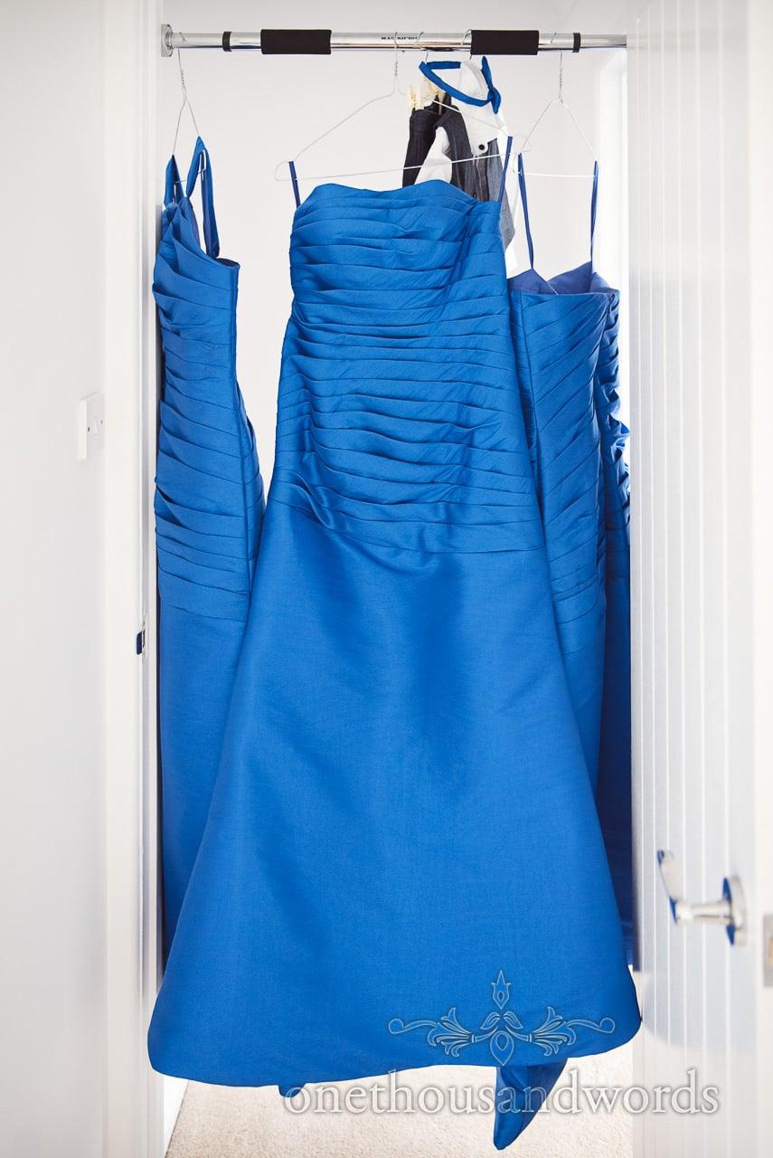 Royal Blue bridesmaid's dresses hang in doorway on wedding morning