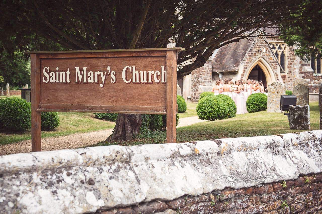 Saint Mary's Church sign outside church with bridesmaids in pink bridesmaids outfits