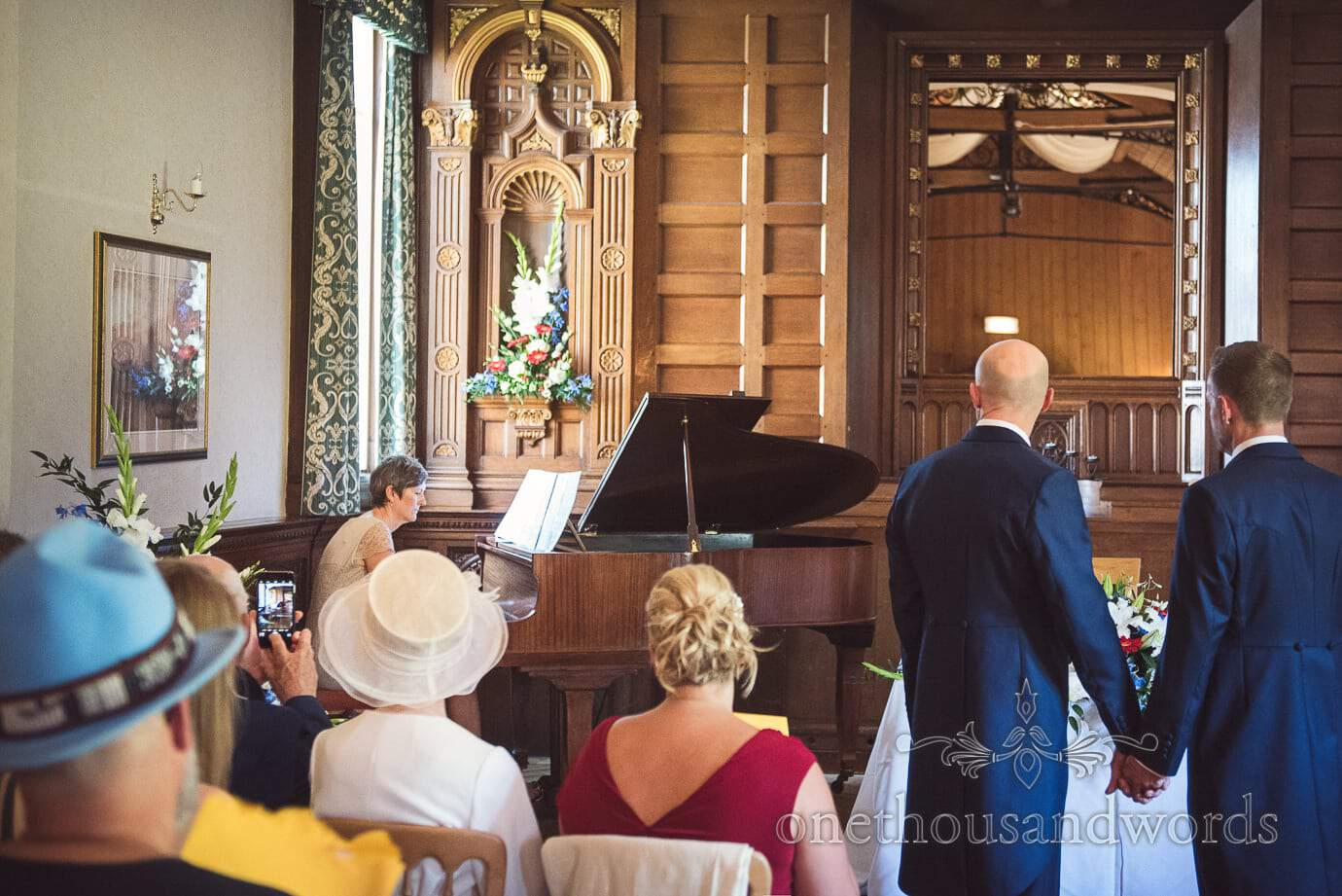 Same sex wedding couple hold hands as piano is played during wedding ceremony