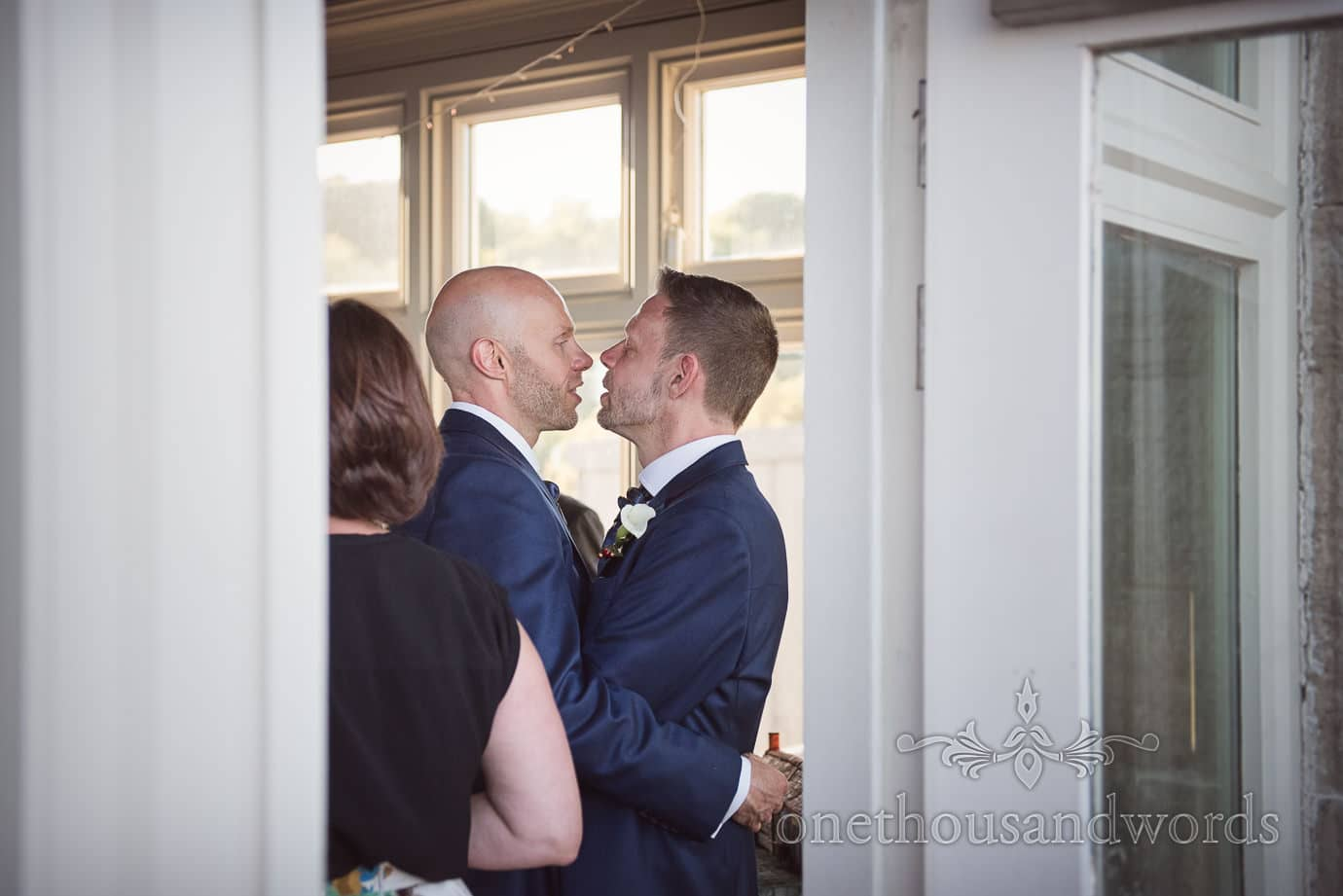Same sex wedding grooms sneak an affectionate kiss before wedding speeches