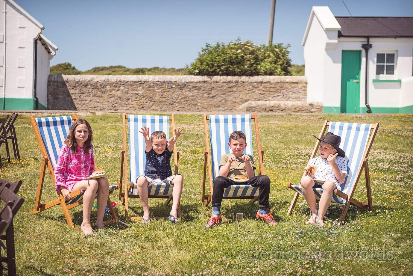 Swanage Wedding Photographers capture child wedding guests in garden deck chairs