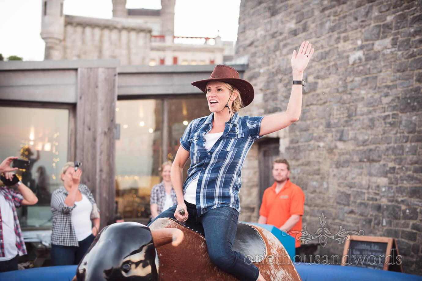 Swanage Wedding Photographers capture cowgirl riding bucking bronco at castle wedding