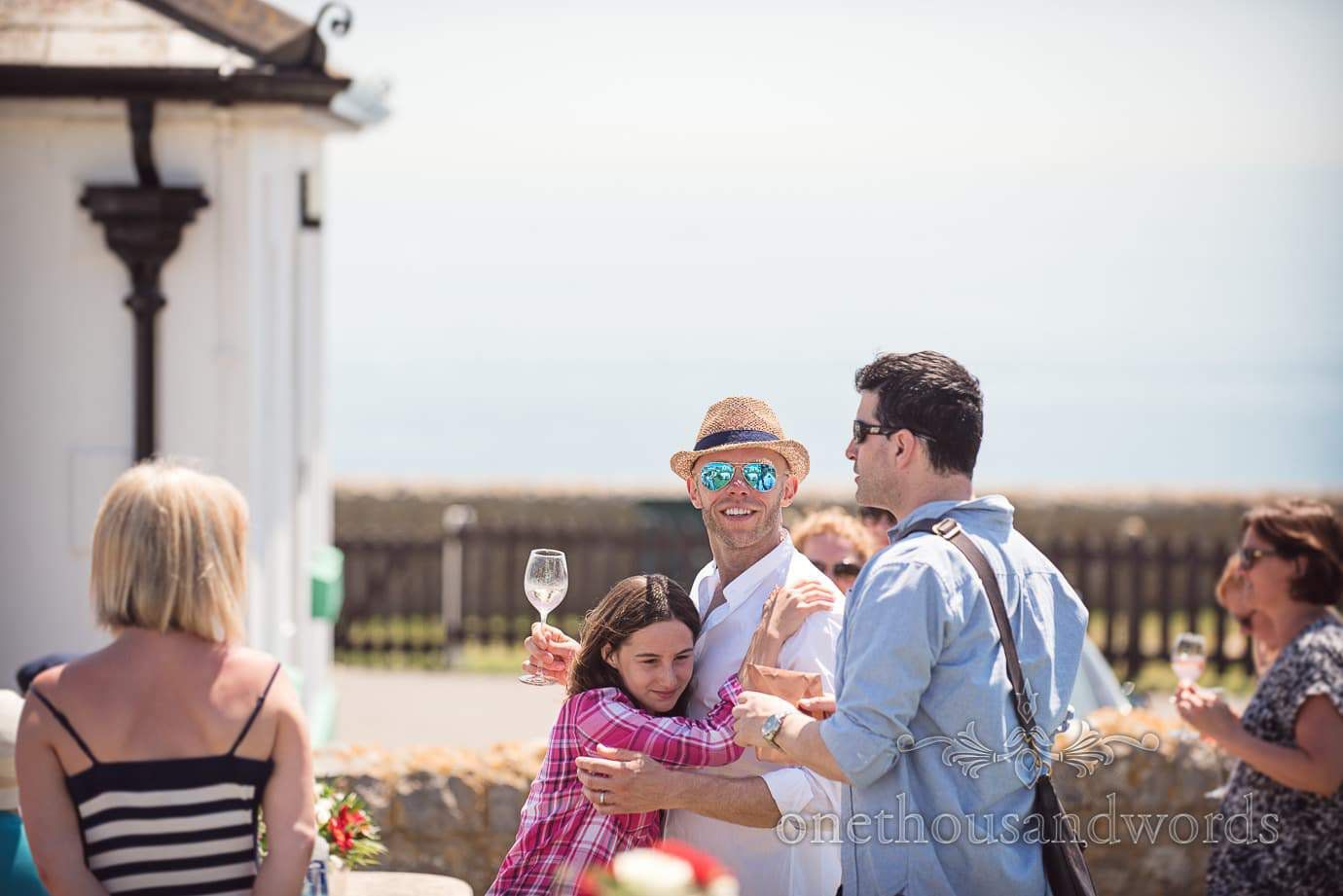 Swanage Wedding Photographers capture groom hugging child wedding guest