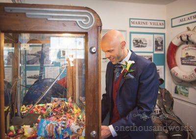 Swanage Wedding Photographers capture groom playing antique arcade games