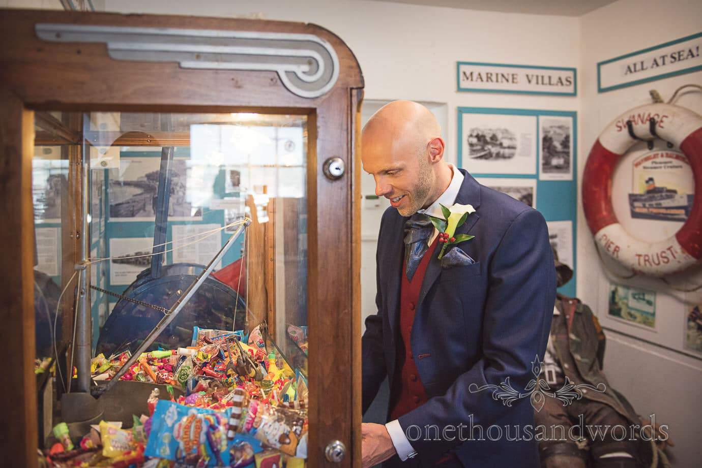 Swanage Wedding Photographers capture groom playing antique arcade games