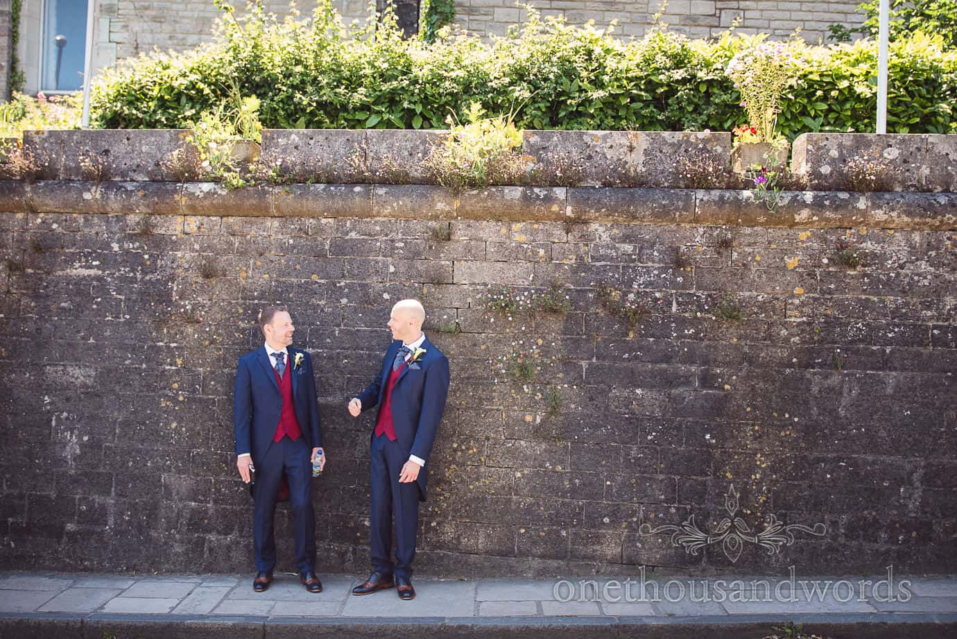 Swanage Wedding Photographers capture grooms next to stone wall waiting for wedding