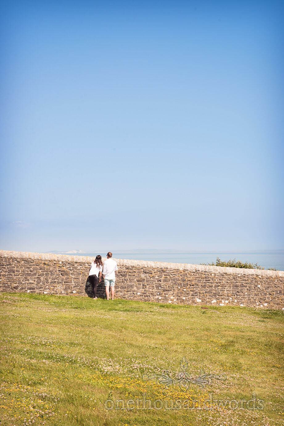 Swanage Wedding Photographers capture wedding guests admiring sea views at Durlston Lighthouse wedding