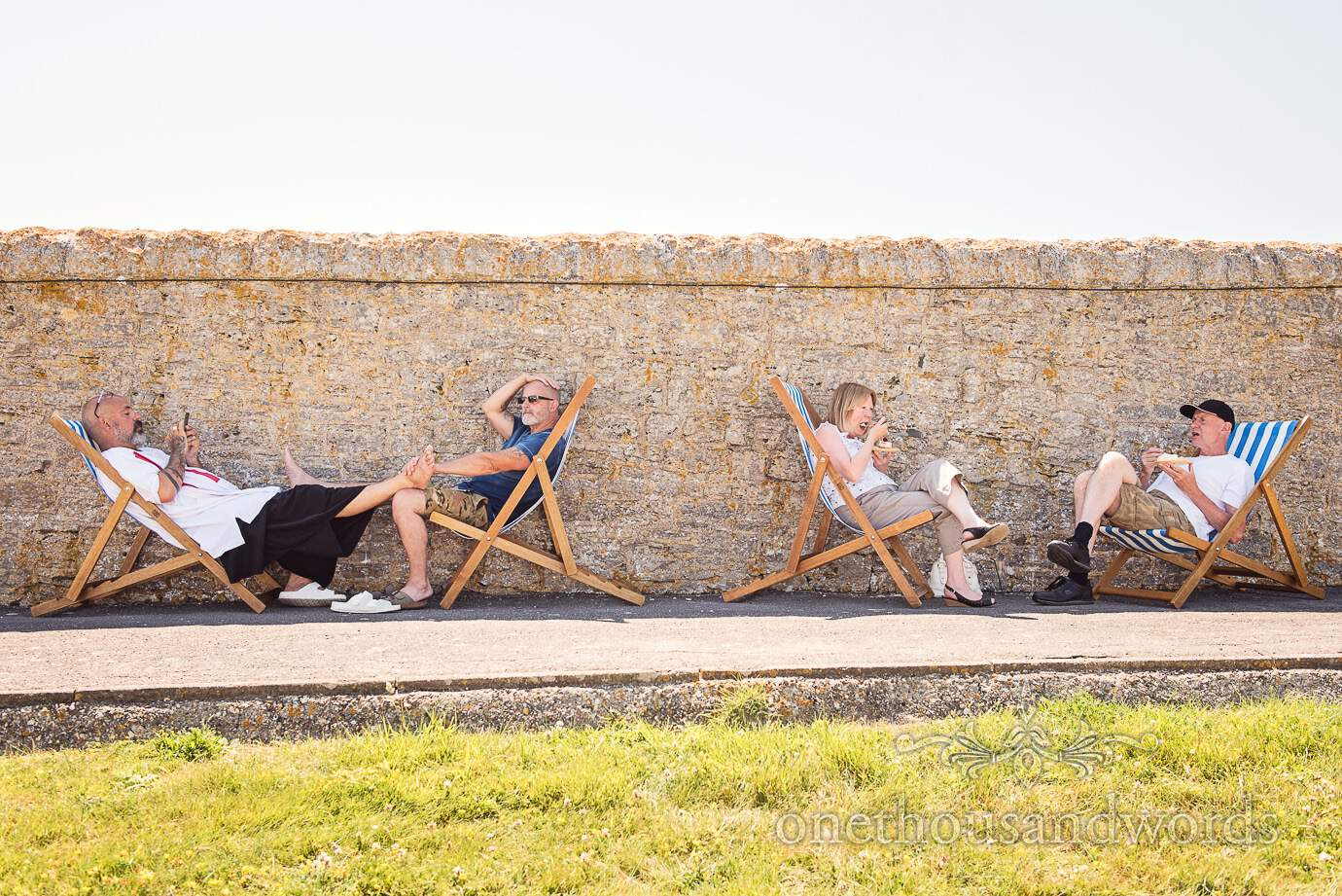 Swanage Wedding Photographers capture wedding guests relaxing in Deck chairs