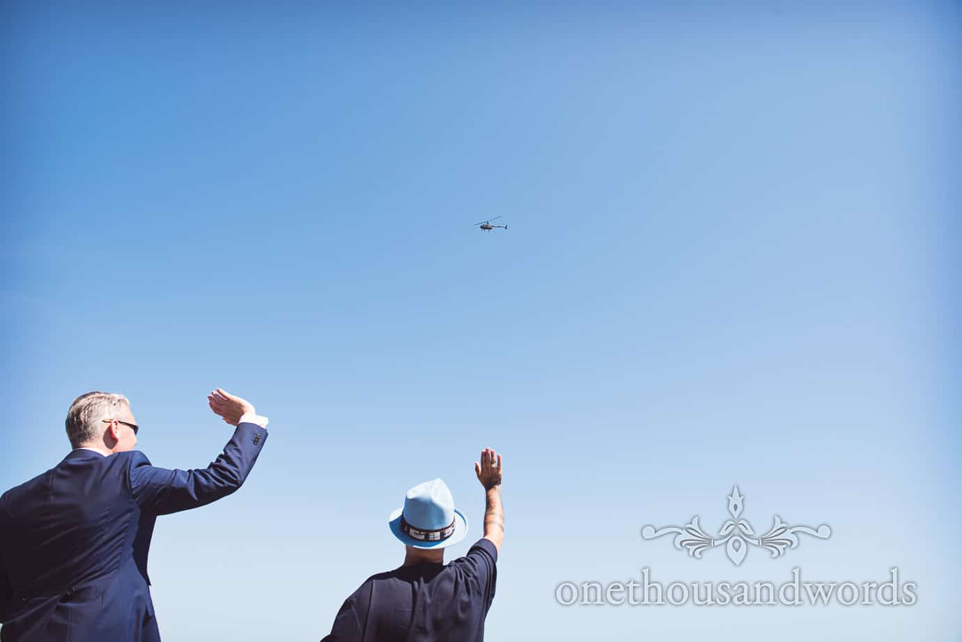Swanage Wedding Photographers capture wedding guests waving at wedding helicopter