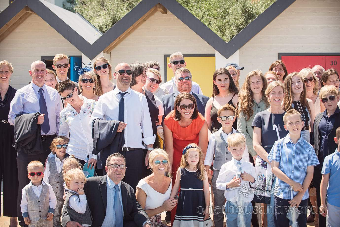 Swanage Wedding Photographers group photograph close up in front of Swanage beach huts