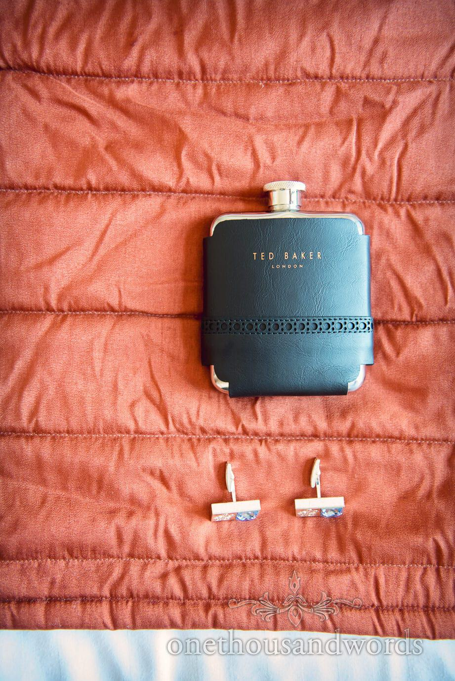 Ted Baker hip flask with silver and blue cuff links on red bed spread on wedding morning