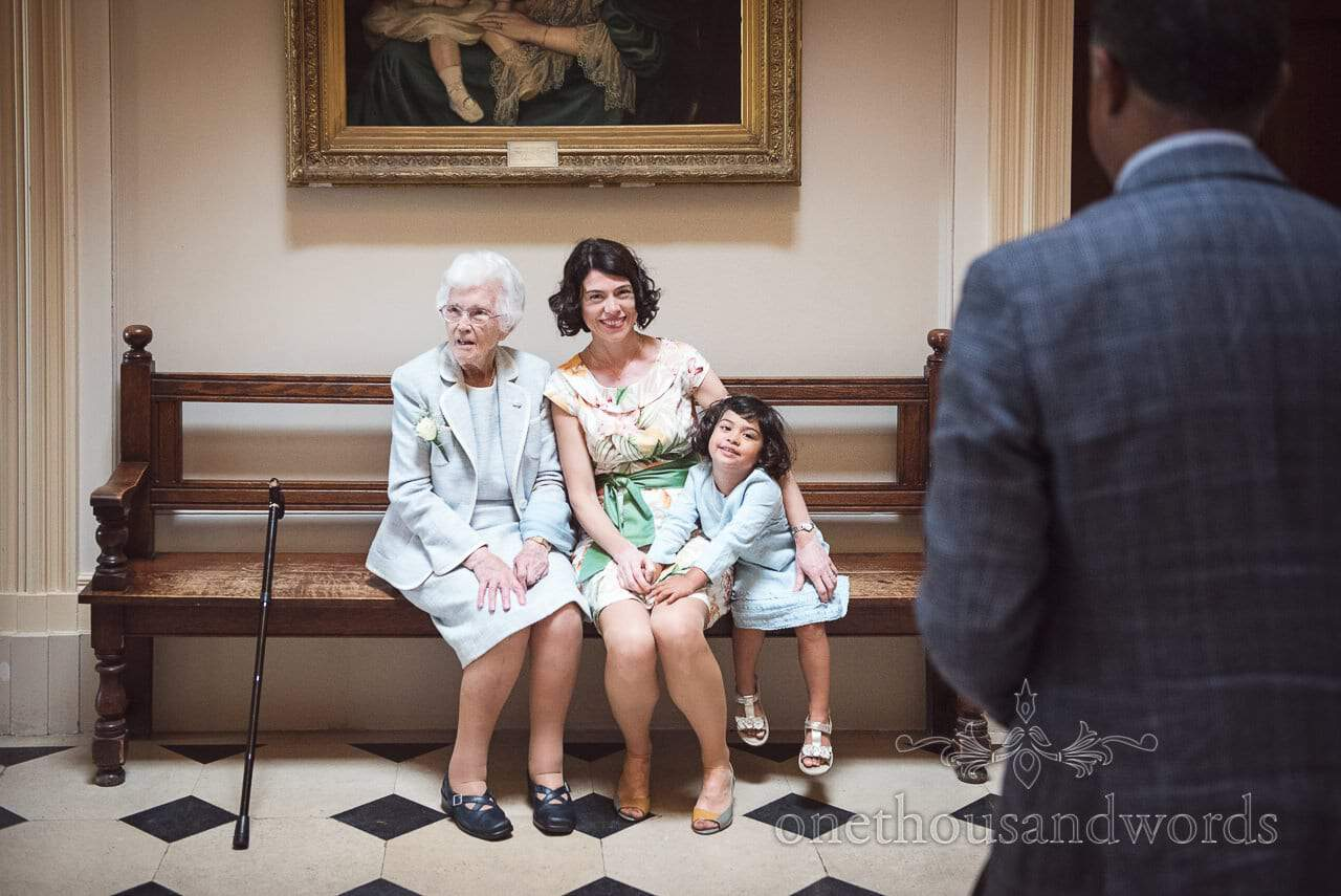 Three generations of wedding guests on bench at Upton House wedding venue in Dorset