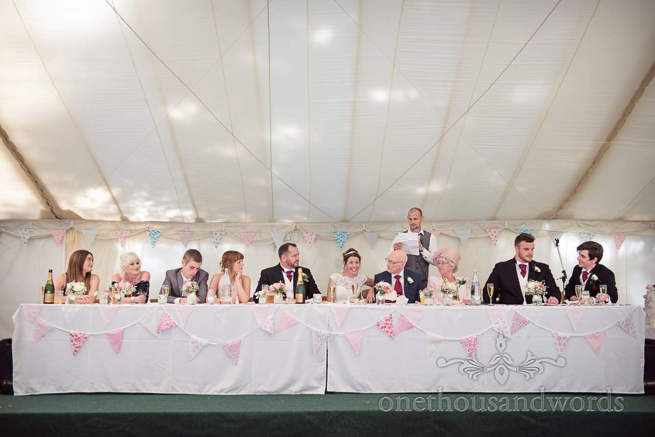 Top table at marquee wedding listens to father of the bride's speech read by his son