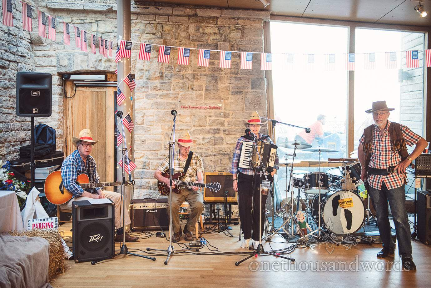 Wedding barn dance band in cowboy outfits with American flags at Durlston Castle wedding