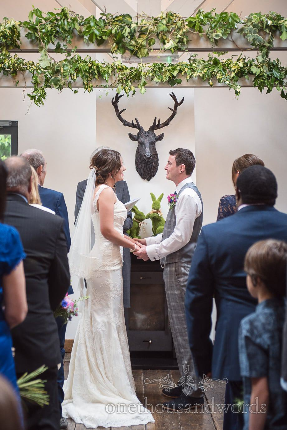Wedding ceremony under ivy with stags head at The Old Vicarage orangery wedding venue