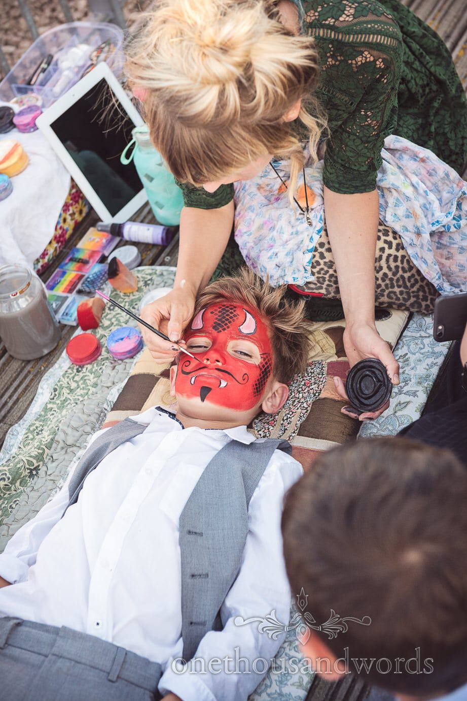 Wedding face painting devil face by Swanage wedding photographers one thousand words