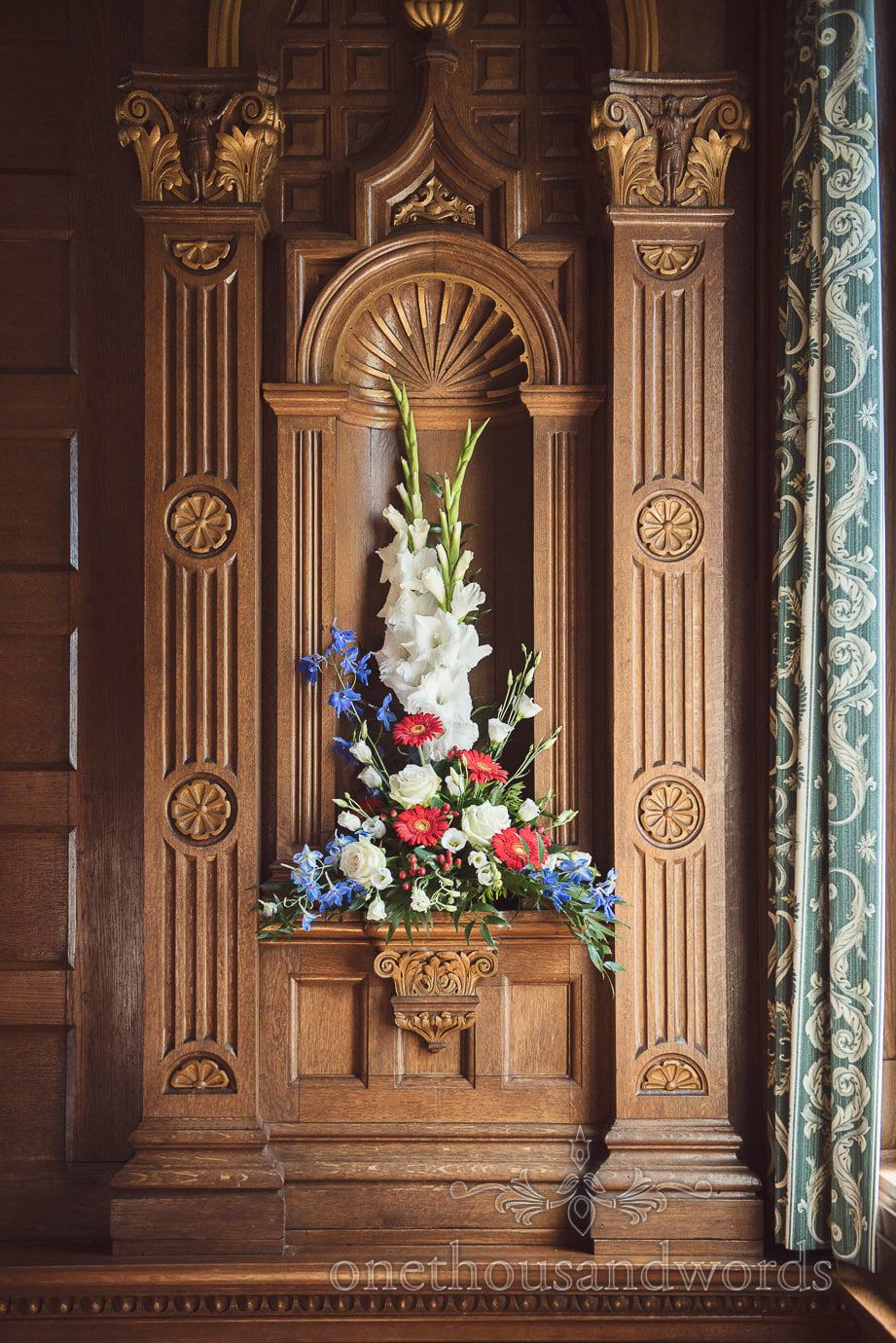 Wedding flowers in carved hard wood wall panelling at Purbeck House Hotel