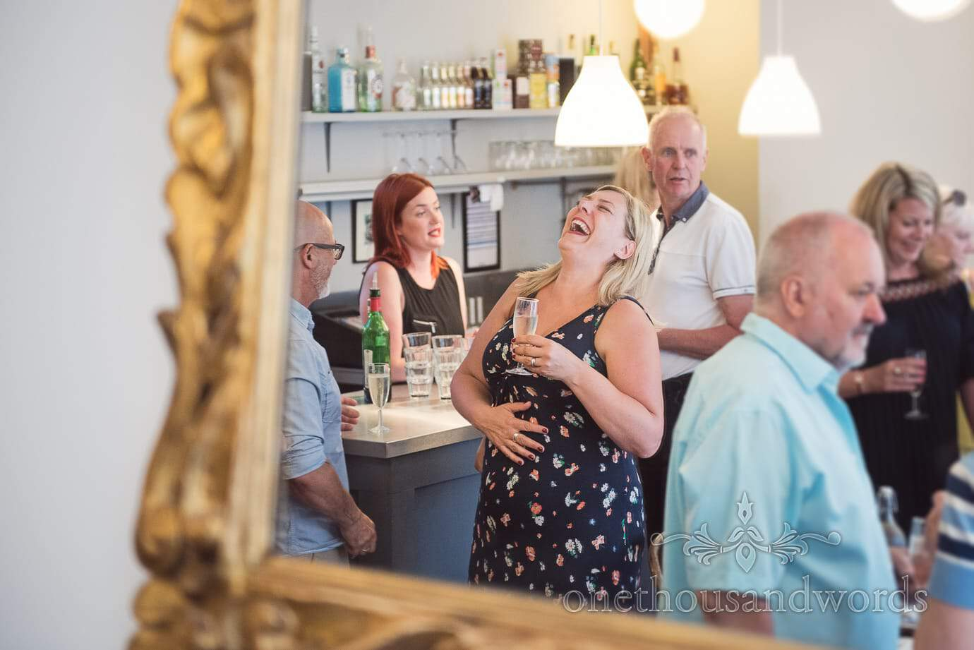 Wedding guest belly laughing in mirror at bar of Swanage pre-wedding restaurant