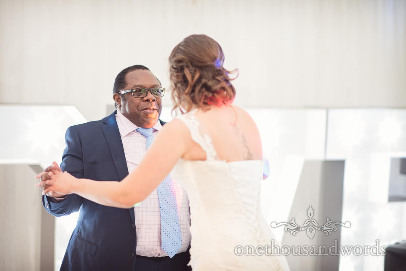 Wedding guest dances with bride against love letters at The Old Vicarage Wedding venue