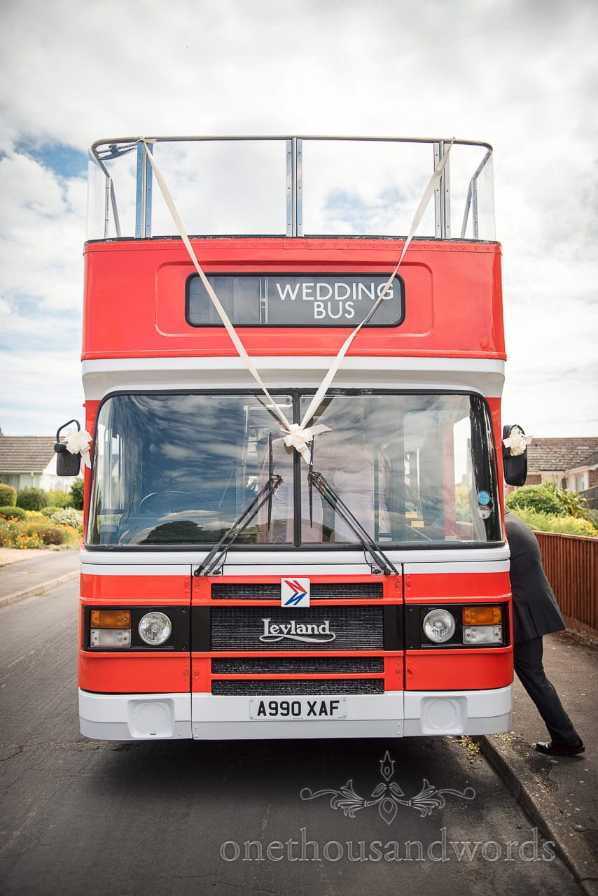 Wedding guest enters Red Layland open top bus wedding transport photograph