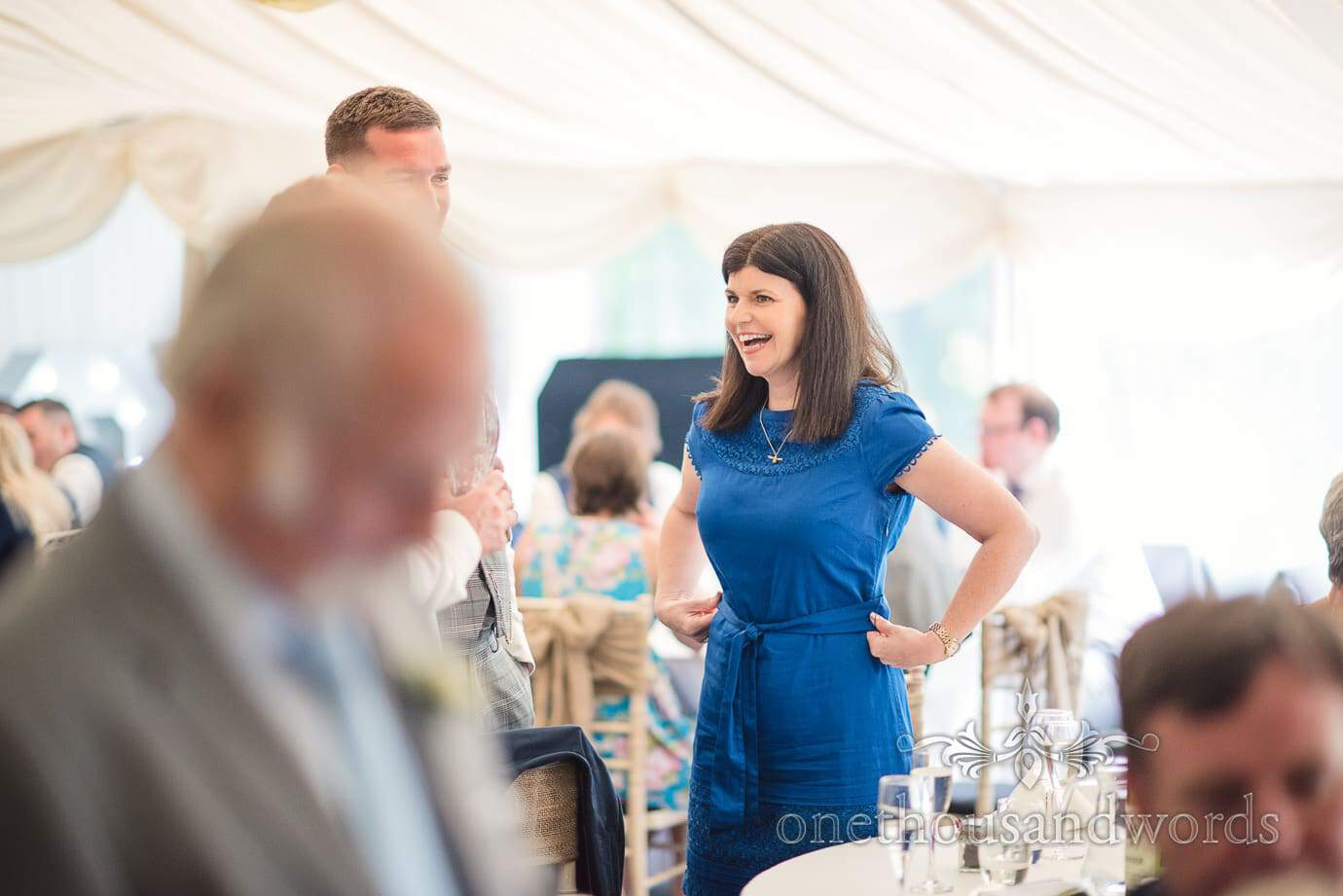 Wedding guest in blue dress laughing at The Old Vicarage marquee Wedding