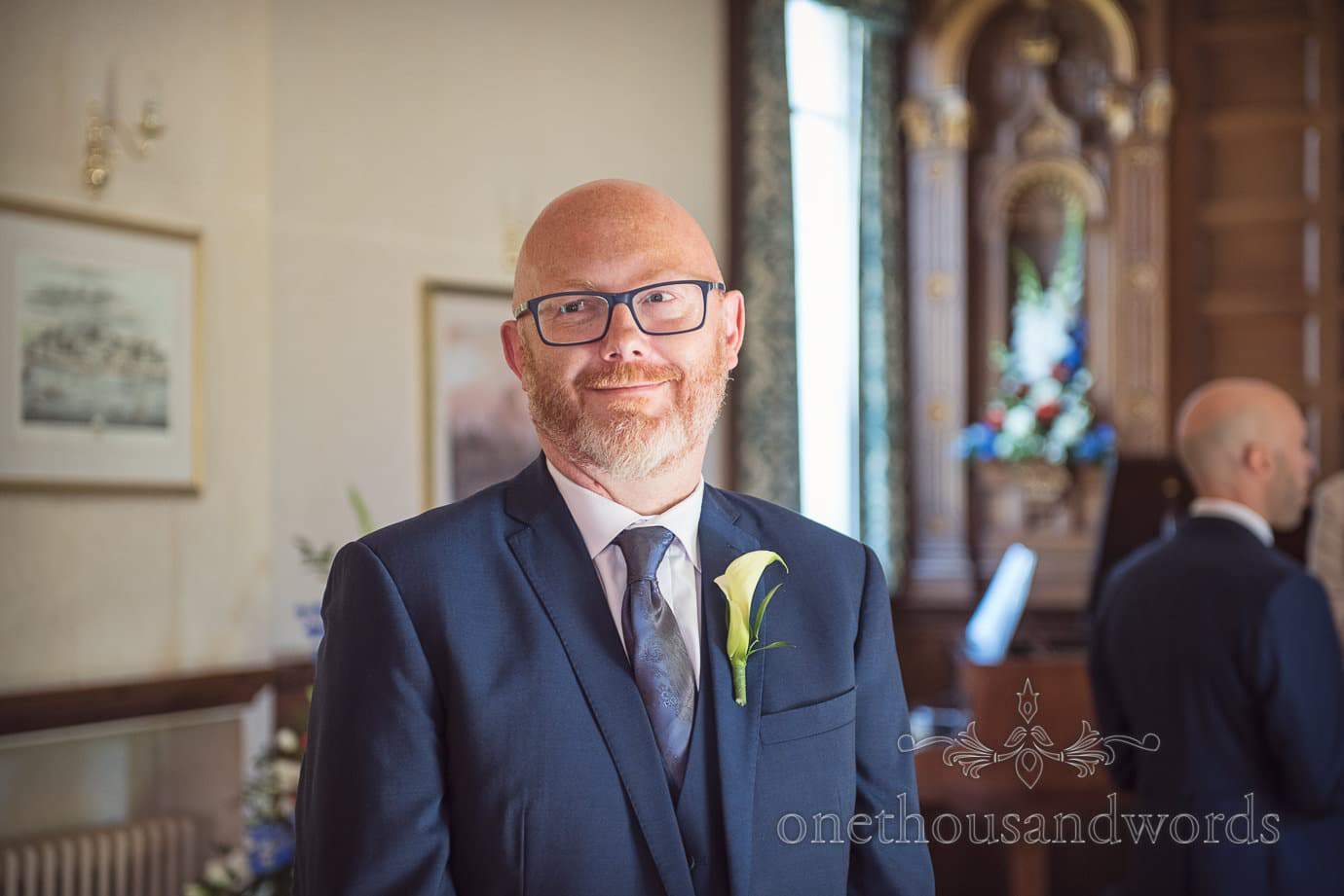 Wedding guest in blue rimmed glasses and blue wedding suit waits at Purbeck House Hotel
