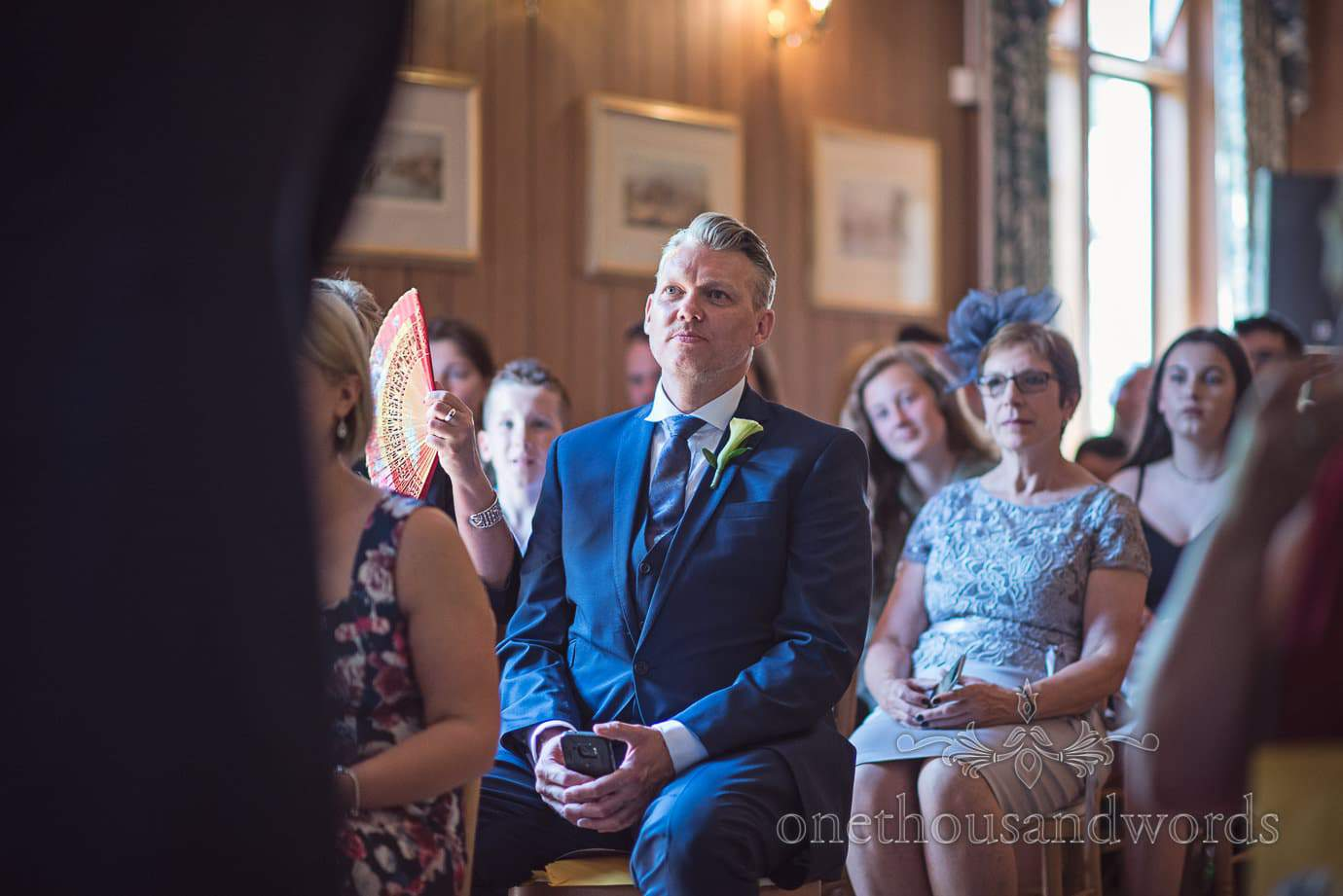 Wedding guest in Blue three piece suit watches wedding ceremony at Purbeck House Hotel