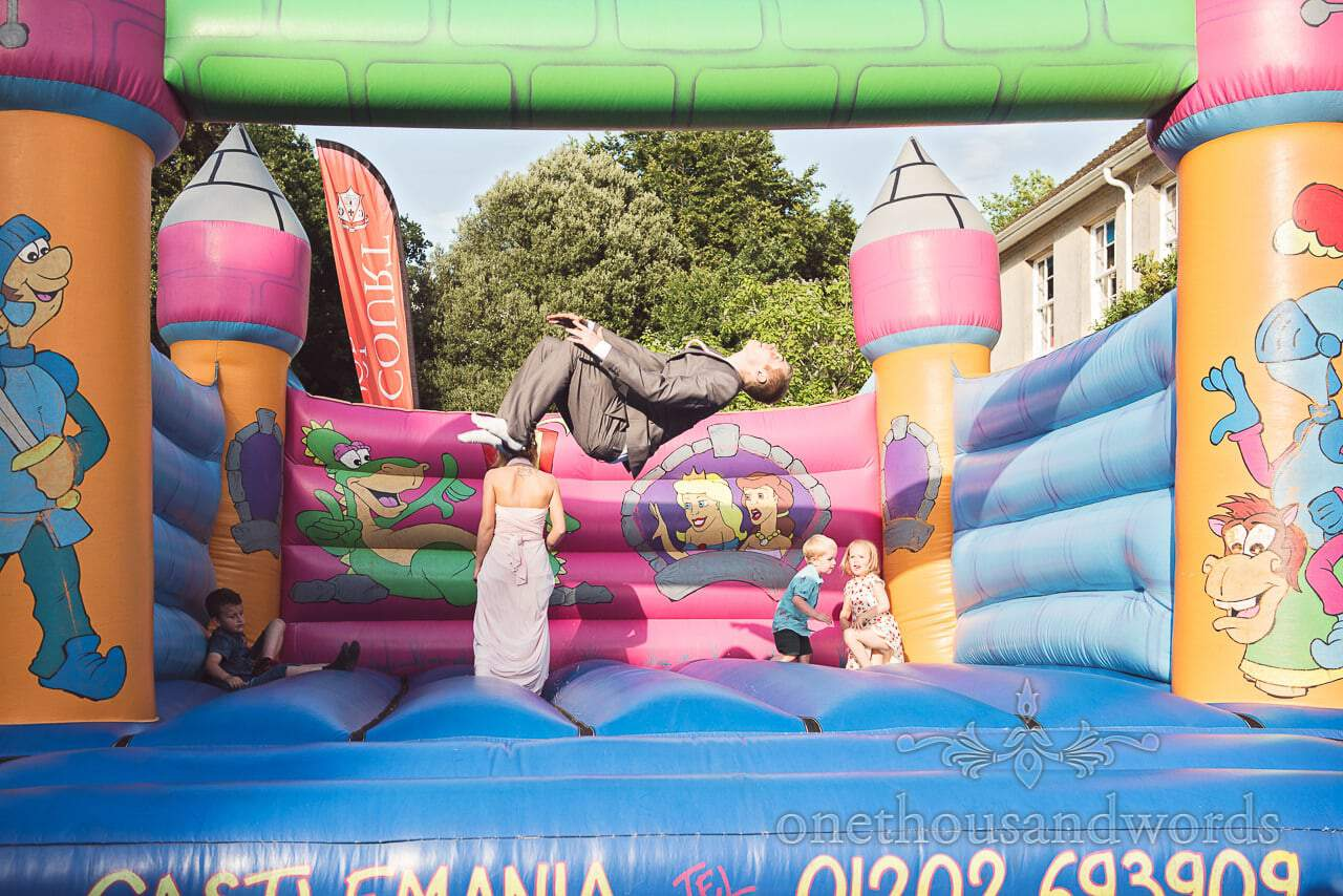 Wedding guest in grey suit in mid air executing backflip on bouncy castle