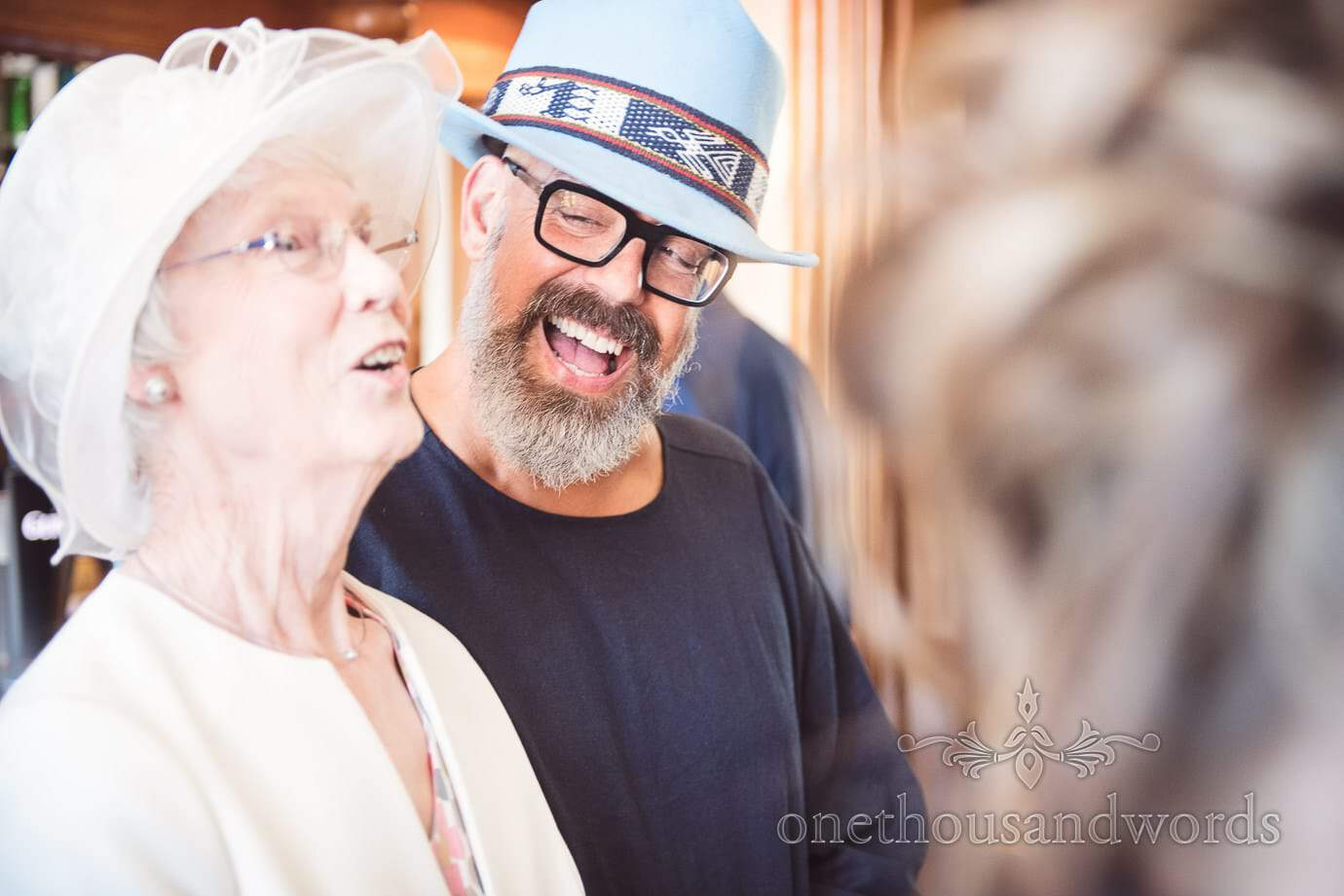 Wedding guest in large blue hat portrait photograph laughing with mother of the groom