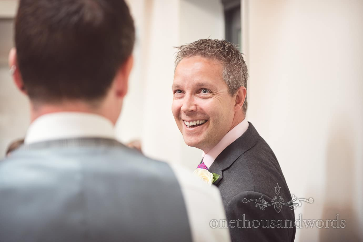 Wedding guest in Salmon shirt and dark get suit laughs at Old Vicarage wedding ceremony