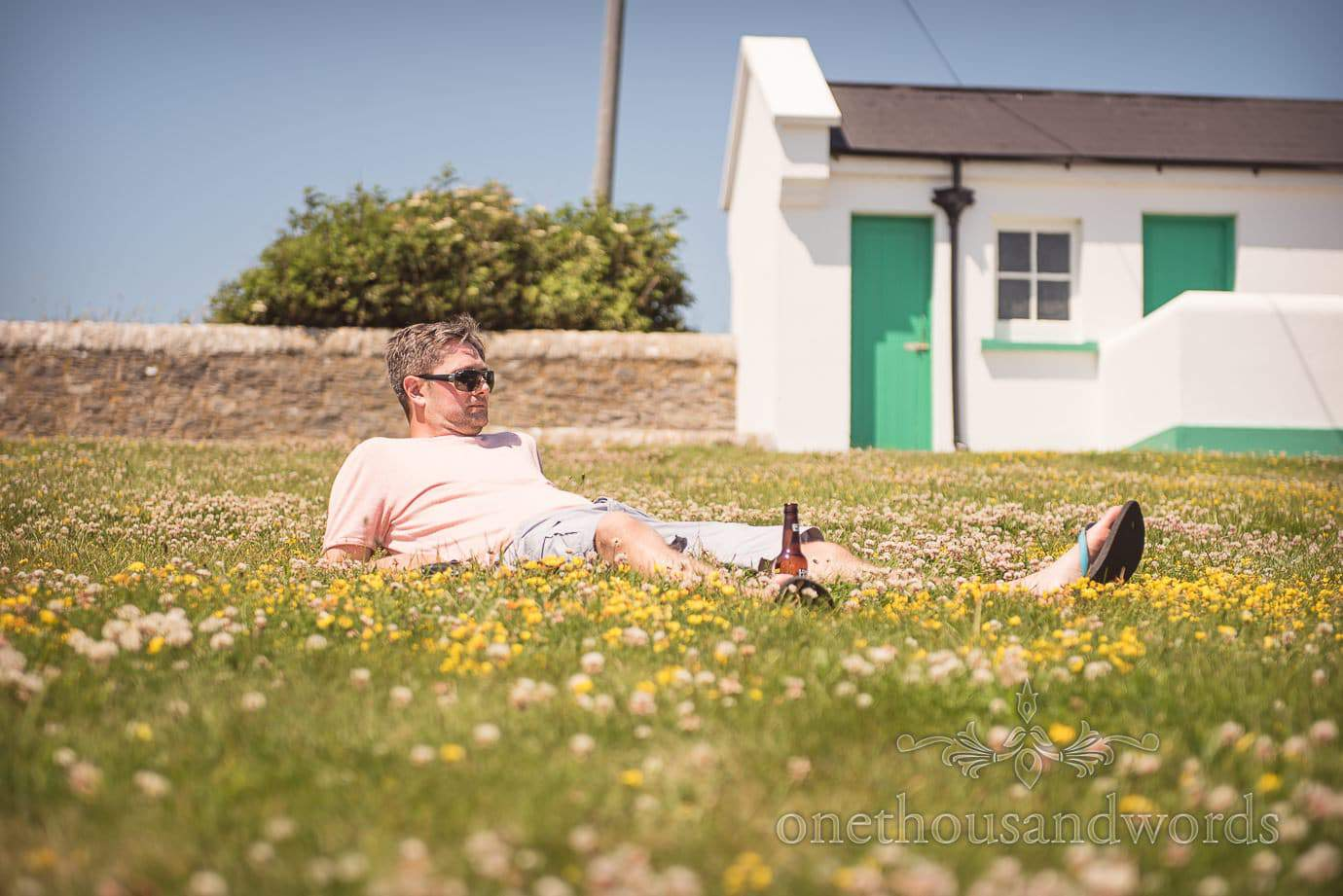Wedding guest relaxes in the sun with a beer on the lawn by Swanage Wedding Photographers