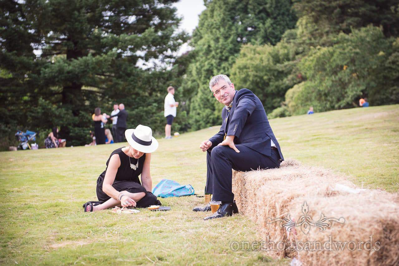 Wedding guest sits on hay bale at countryside wedding in Dorset by one thousand words
