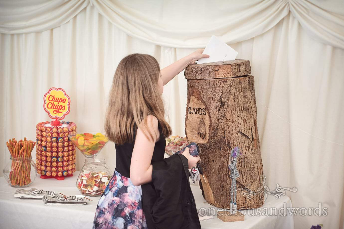 Wedding guest uses wooden log cards box at The Old Vicarage marquee Wedding