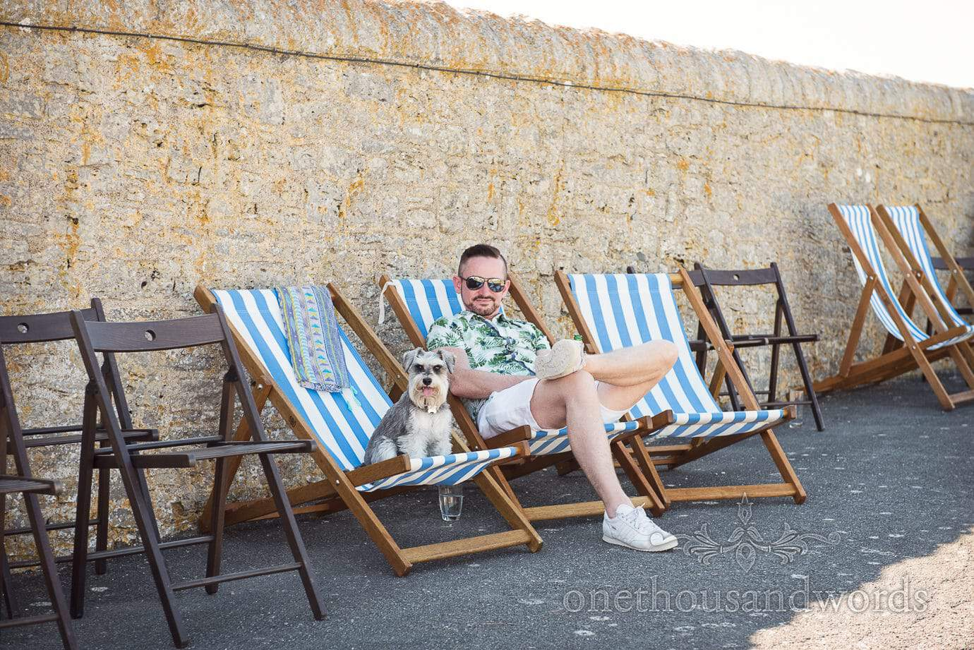 Wedding guest with small dog in striped deck chairs at post wedding party