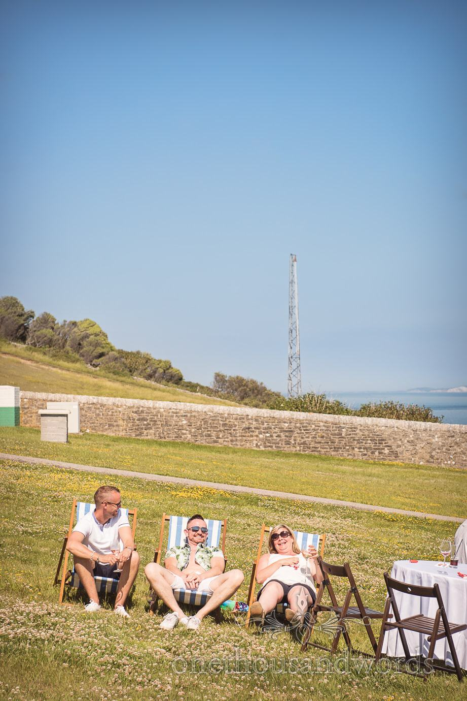 Wedding guests in deck chairs in Durlston Lighthouse gardens with the sea and Isle of Wight view