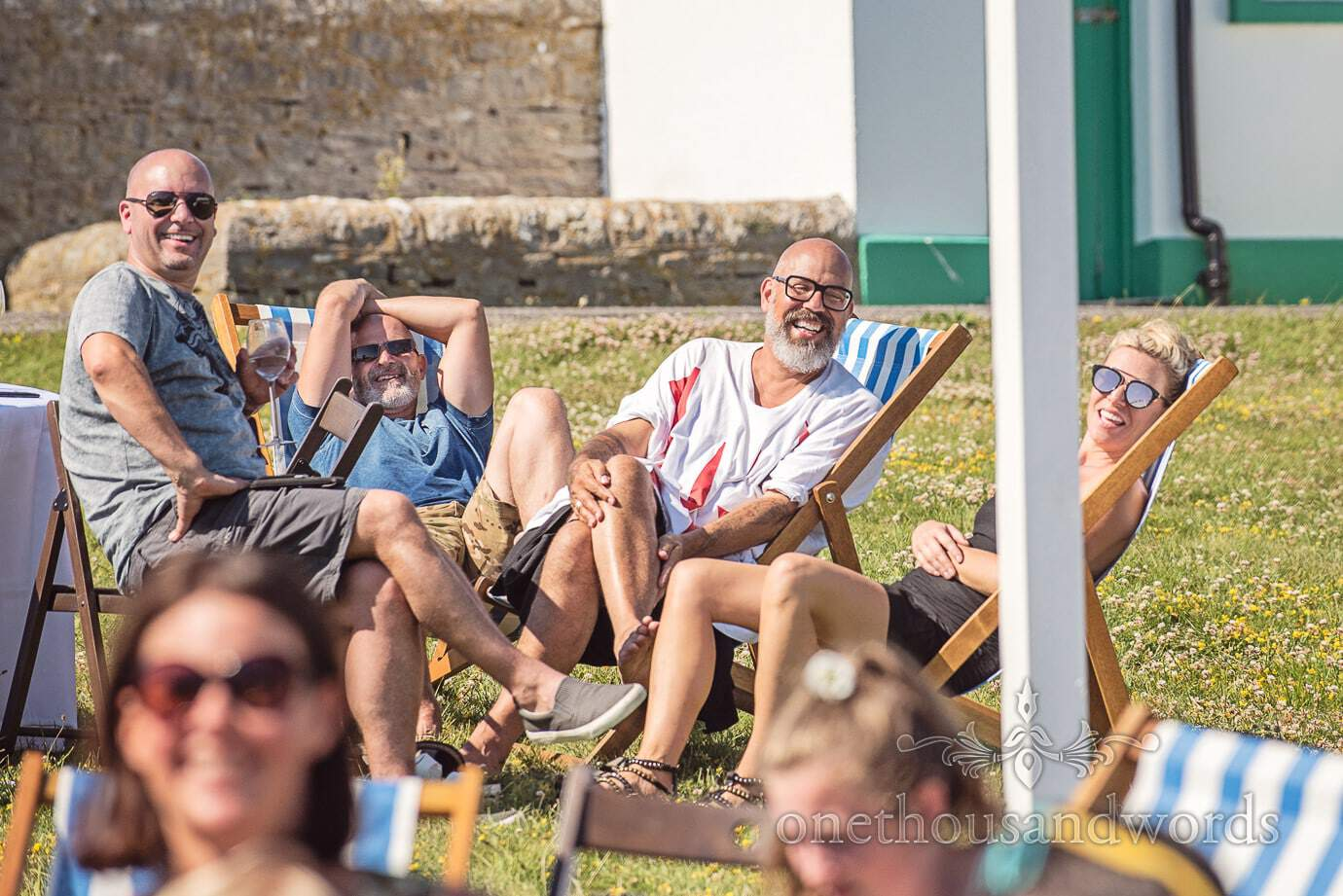 Wedding guests in deck chairs laughing at Durlston Lighthouse by Swanage Wedding Photographers