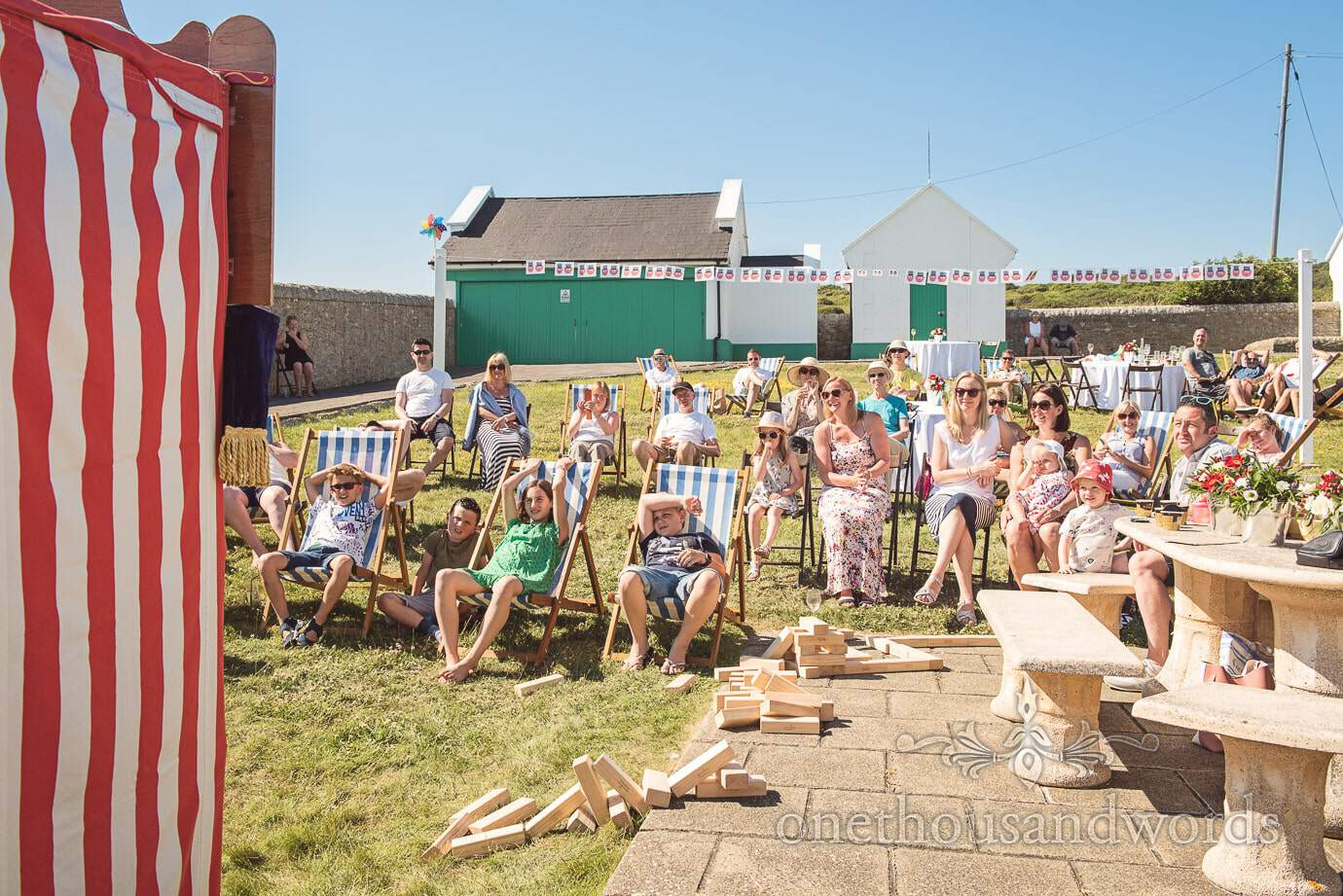 Wedding guests in deck chairs watch Punch and Judy at Durlston Lighthouse wedding