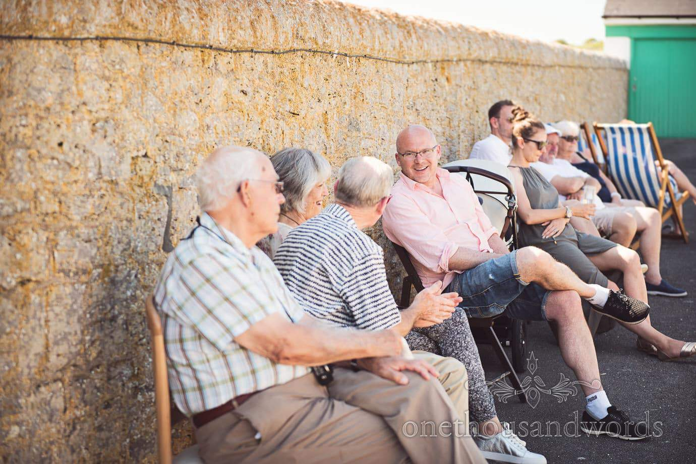 Wedding guests in deckchairs shelter in shade of a wall at Durlston Lighthouse wedding photographs