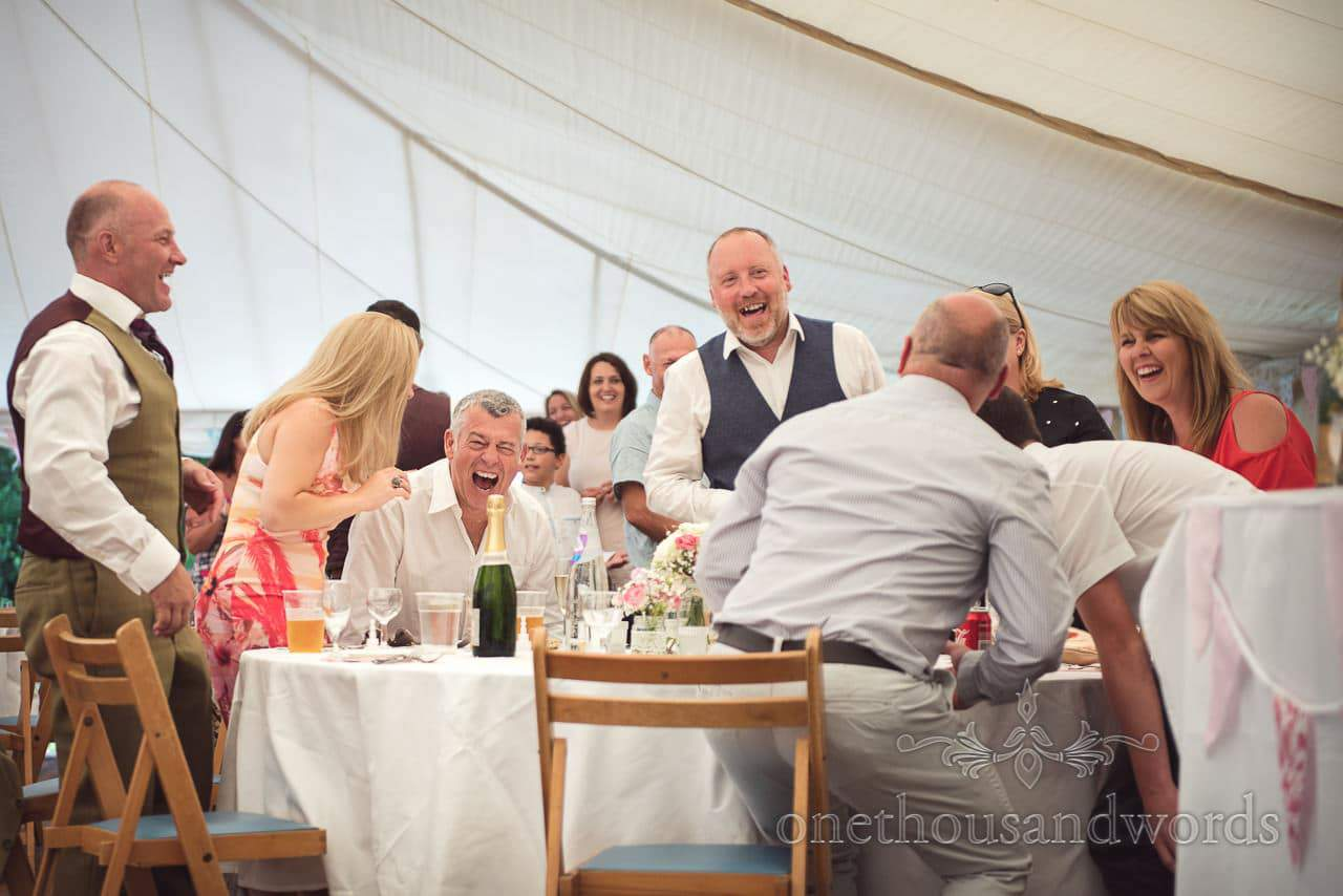 Wedding guests laughing at wedding speeches in white wedding marquee