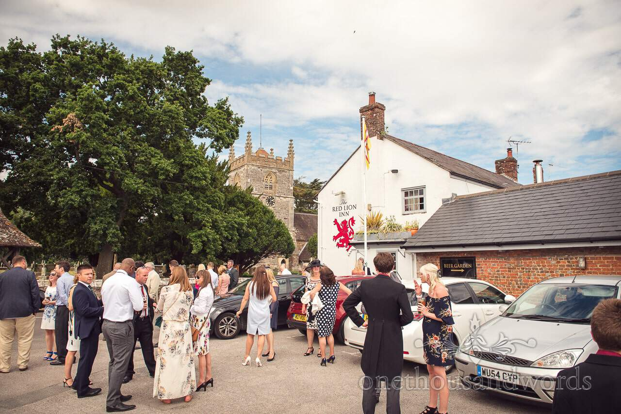Wedding guests outside red lion pub and old English stone church wedding venue
