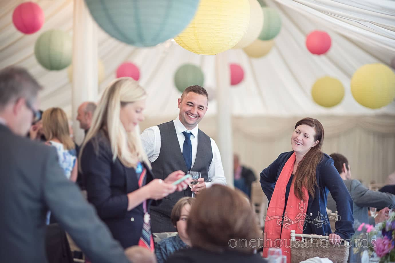 Wedding guests share jokes in marquee at The Old Vicarage Wedding venue