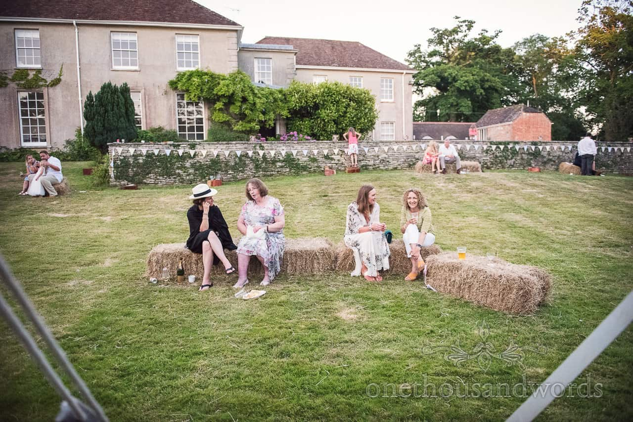 Wedding guests sit on hay bales at countryside marquee wedding in Dorset