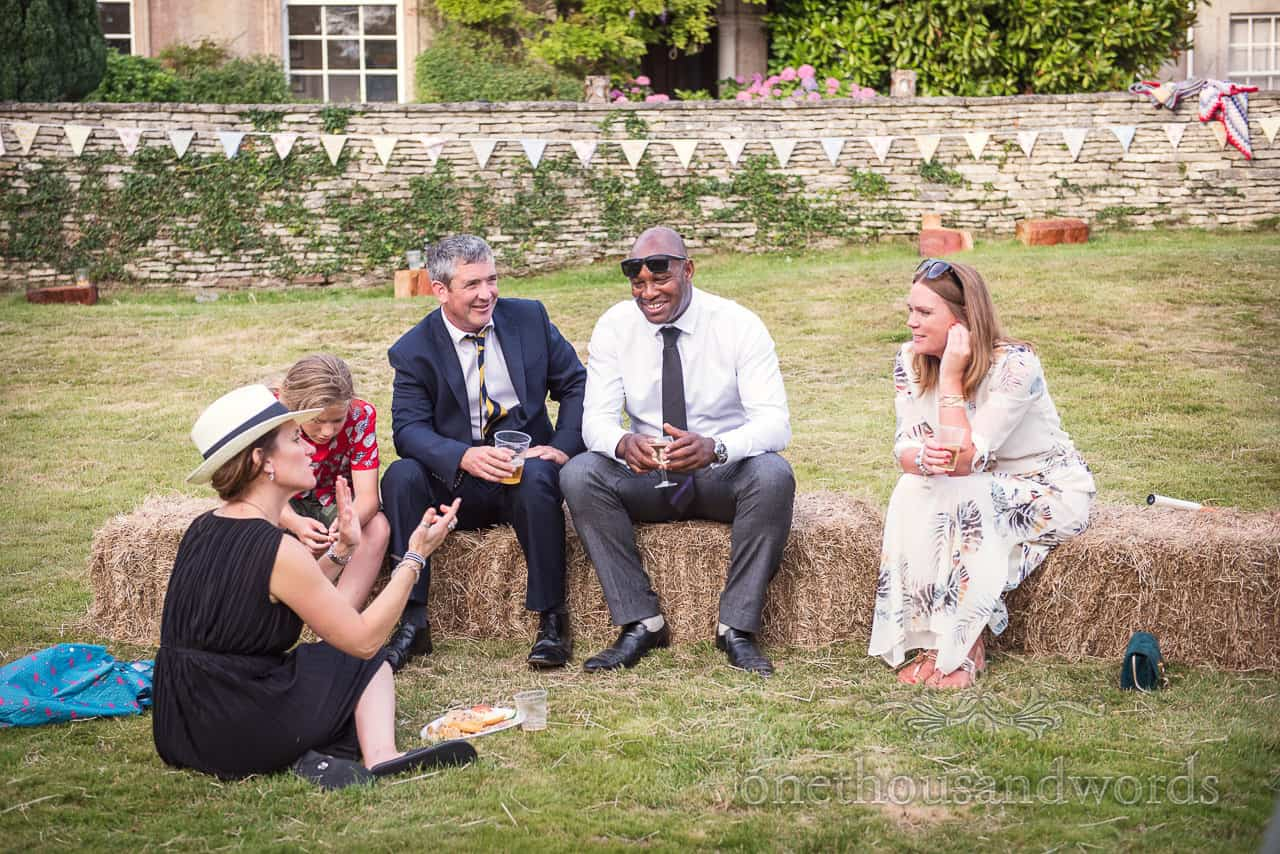 Wedding guests sit on hay bales during wedding evening reception