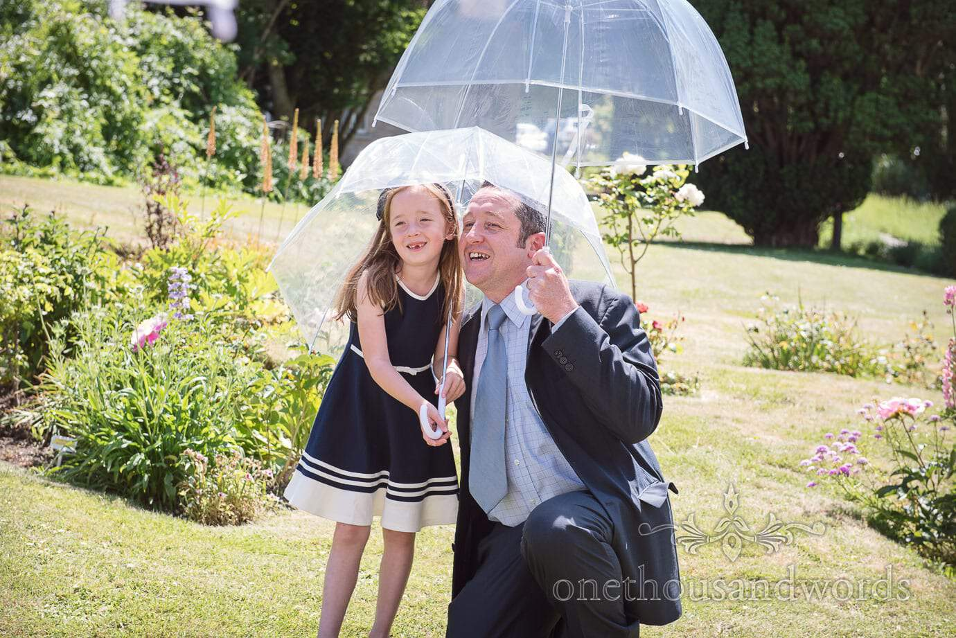 Wedding guests under see through umbrellas in the gardens at Purbeck House Hotel wedding