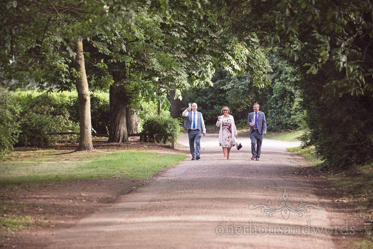 Wedding guests walking through Upton House country park wedding venue