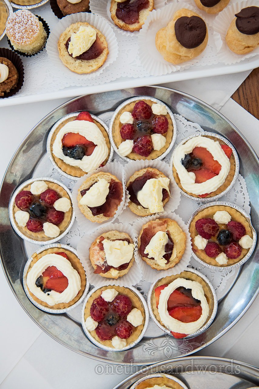 Wedding high tea cakes, scones and tarts photographed from above on silver tray