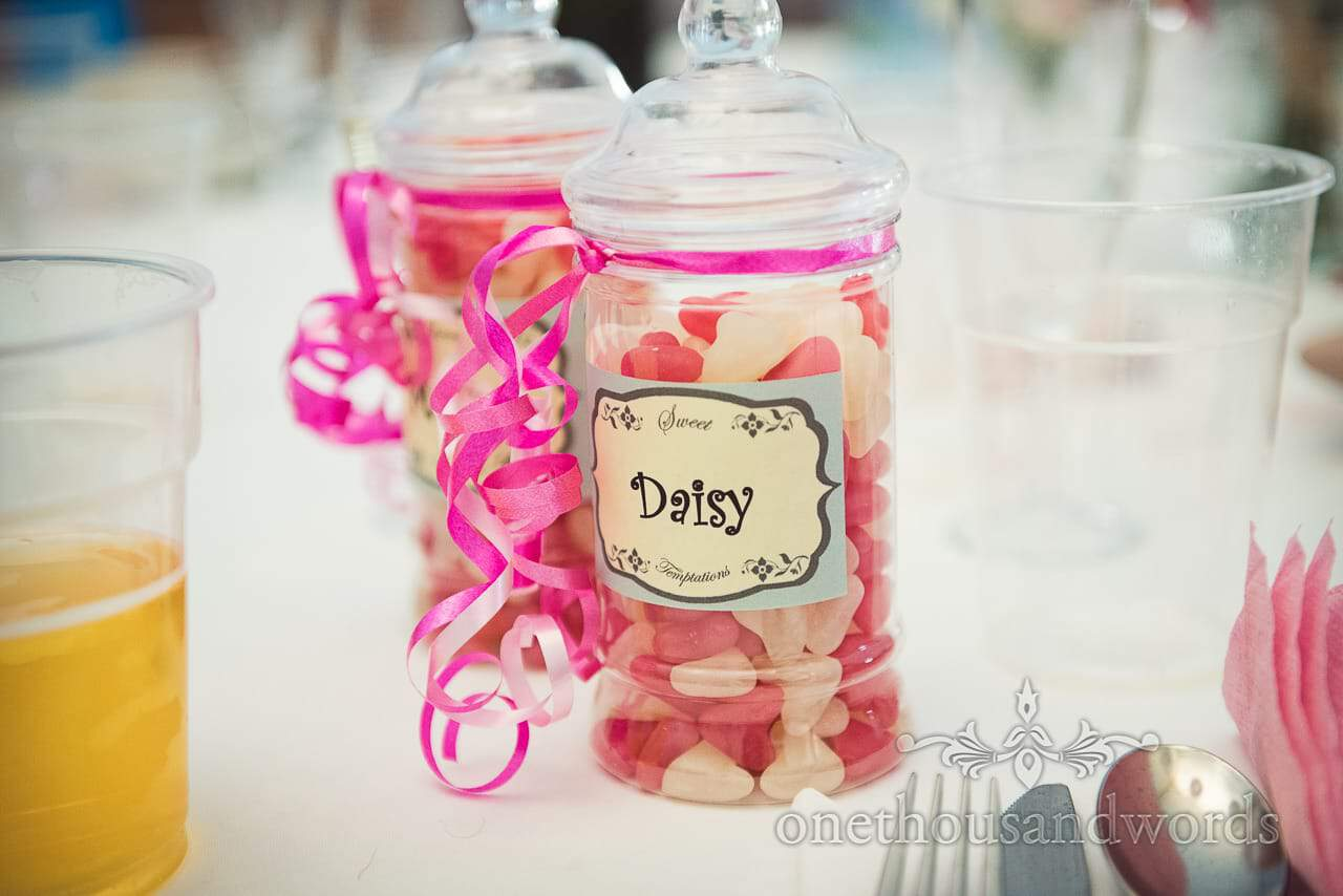 Wedding sweets in jar with pink ribbon as wedding favours with label for daisy