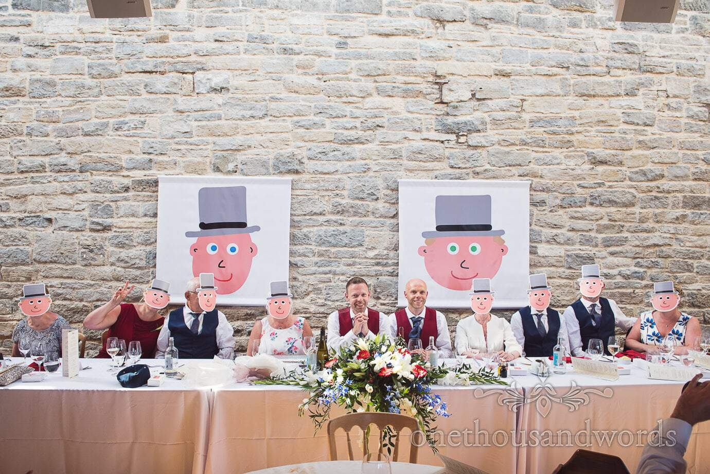 Wedding top table wearing cartoon groom masks at gay wedding in Swanage, Dorset